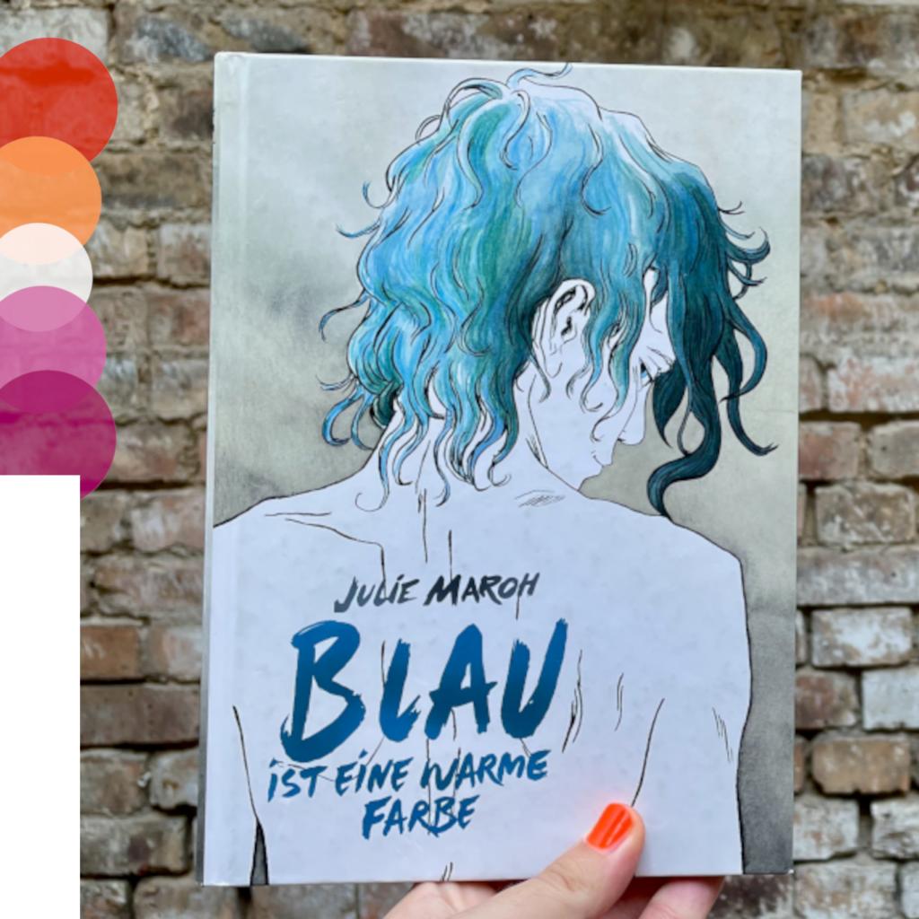 Eine Hand hält das Buchcover von »Blau ist eine warme Farbe« vor einer Steinwand. Auf der linken Bildseite sind Kreise in den Farben der Lesbischen-Pride-Flagge zu sehen.