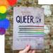 Eine Hand hält das Cover von »Queer. Eine illustrierte Geschichte« vor einer Steinwand. In der linken oberen Ecke sind Kreise in den Farben der Regenbogen-Flagge.