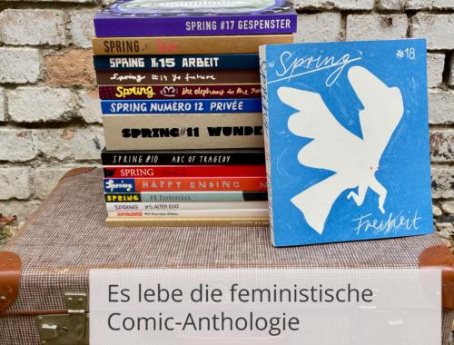 Vor einer Steinwand steht ein Koffer auf dem ein Stapel mit den SPRING Magazin Ausgaben 3 bis 17. An dem Stapel lehnt die aktuelle Ausgabe 18. Davor steht der Titel des Beitrags: Es lebe die feministische Comic-Anthologie. Das SPRING Magazin #18 über die großen und kleinen Freiheiten.