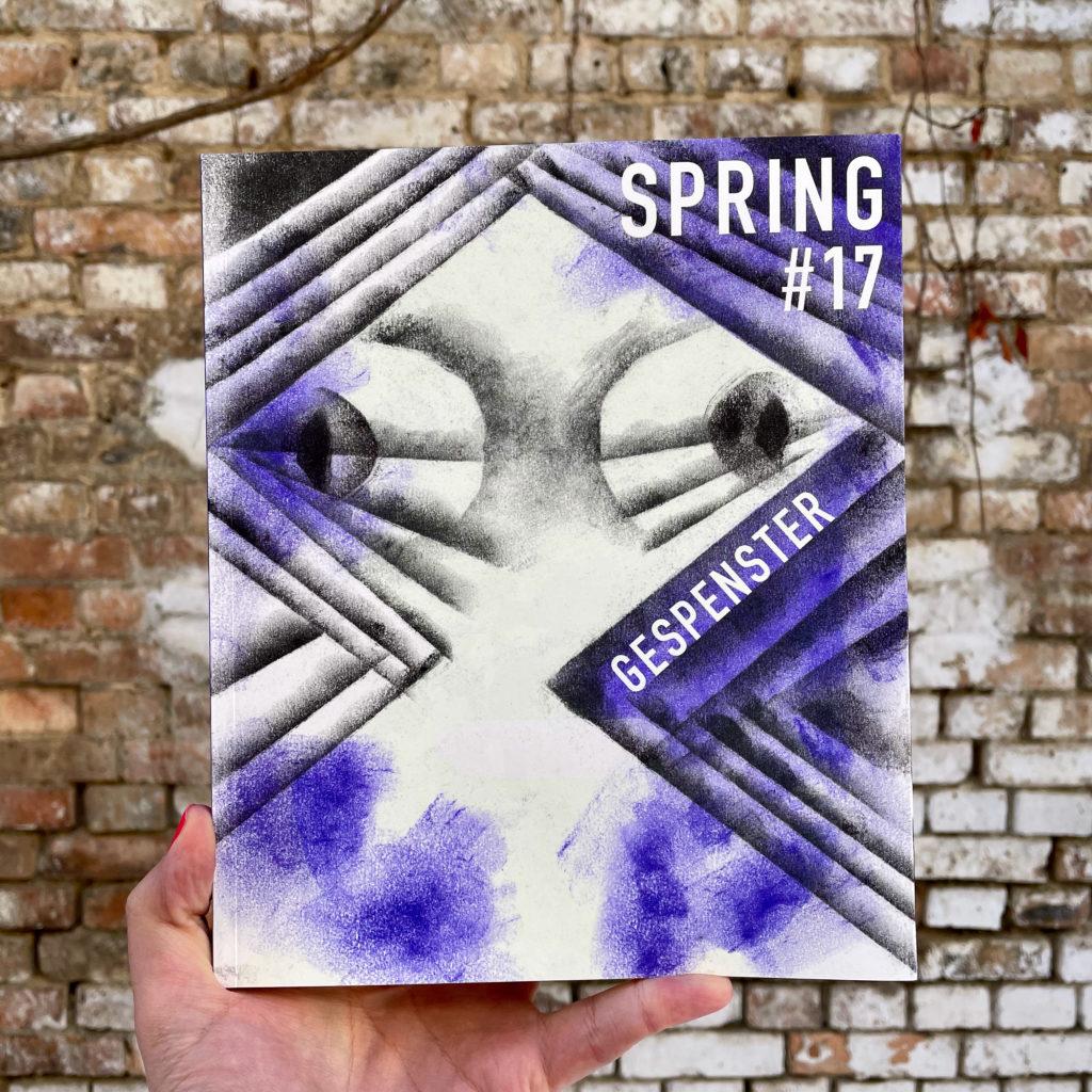 Eine Hand hält das SPRING Magazin #13 Gespenster vor einer Steinwand.