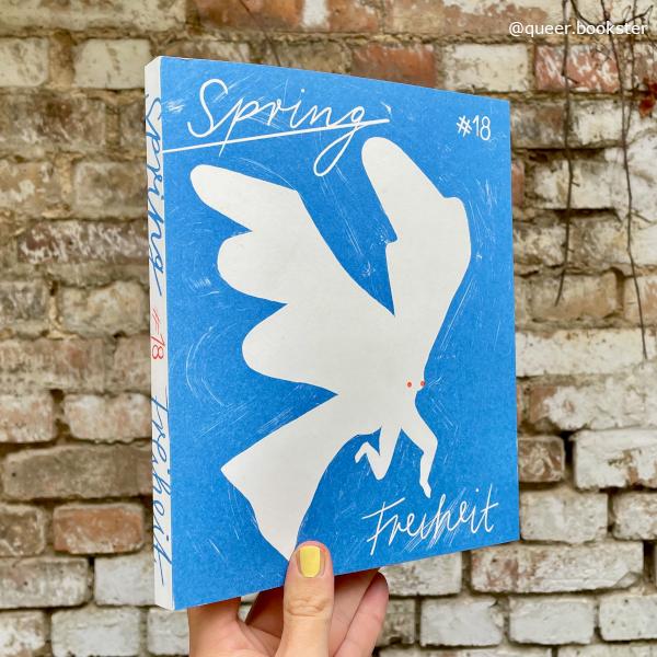 Eine Hand hält das SPRING Magazin #18 Freiheit vor einer Steinwand