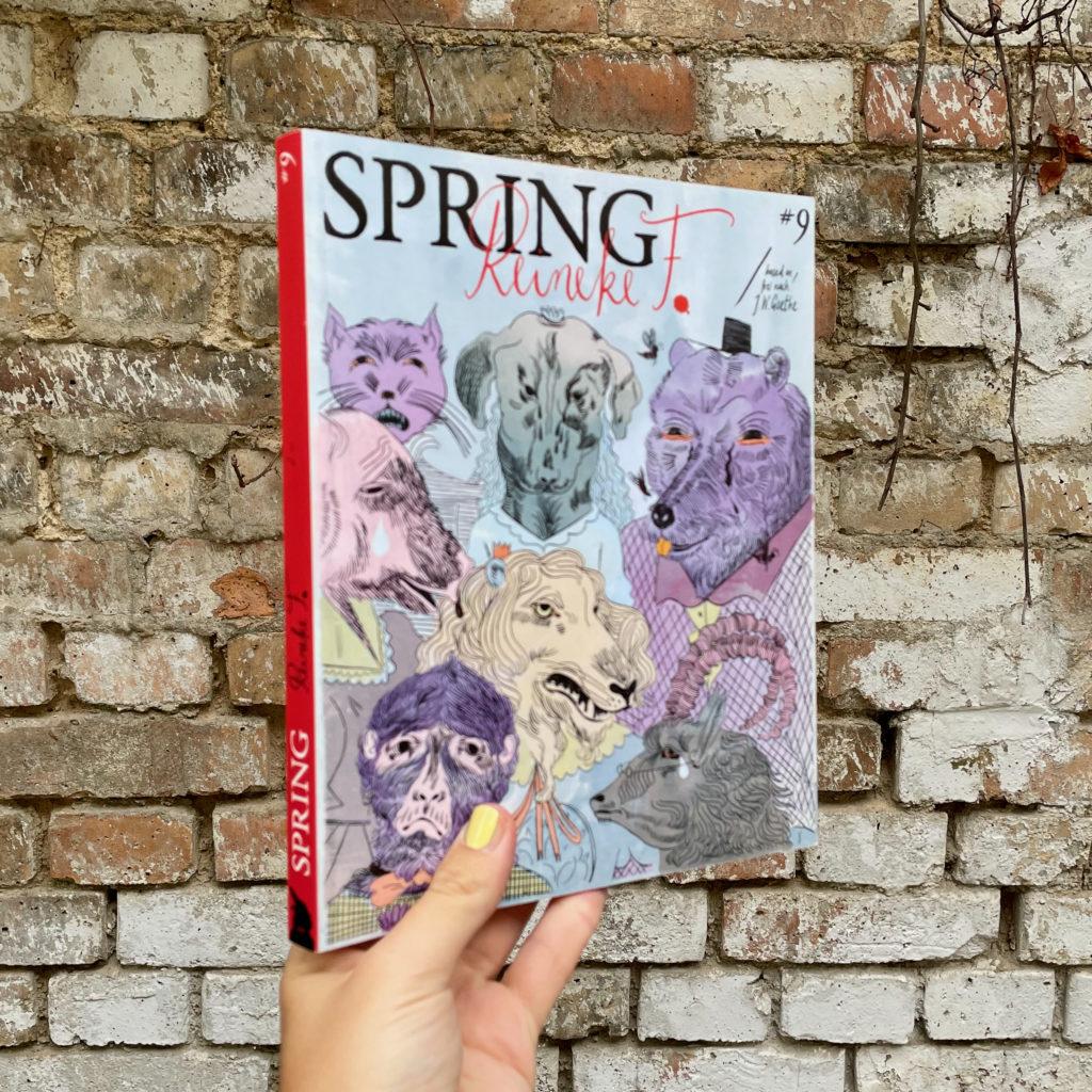 Eine Hand hält das SPRING Magazin #13 Reineke F. vor einer Steinwand.
